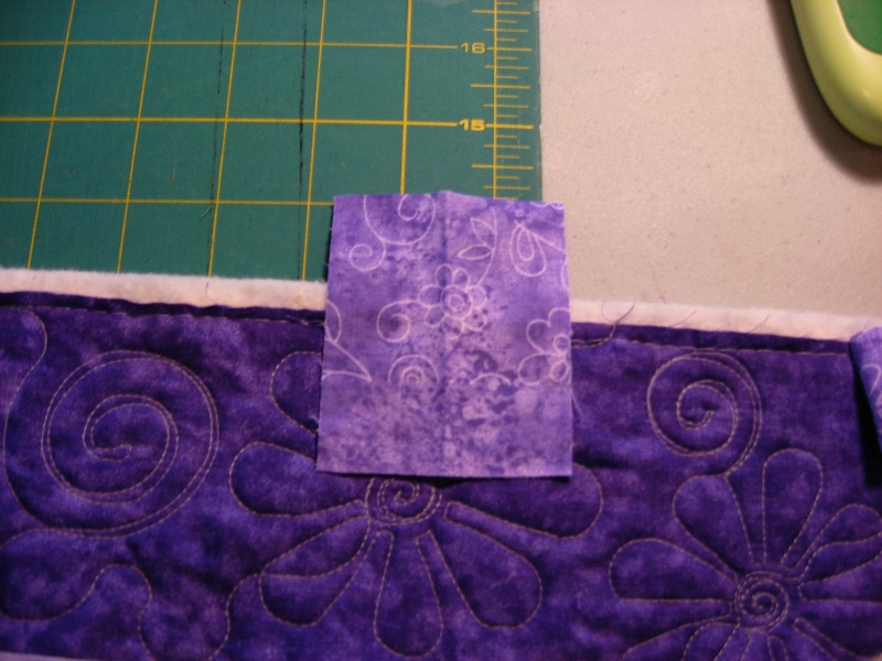 place the scrap of binding across the quilt edge