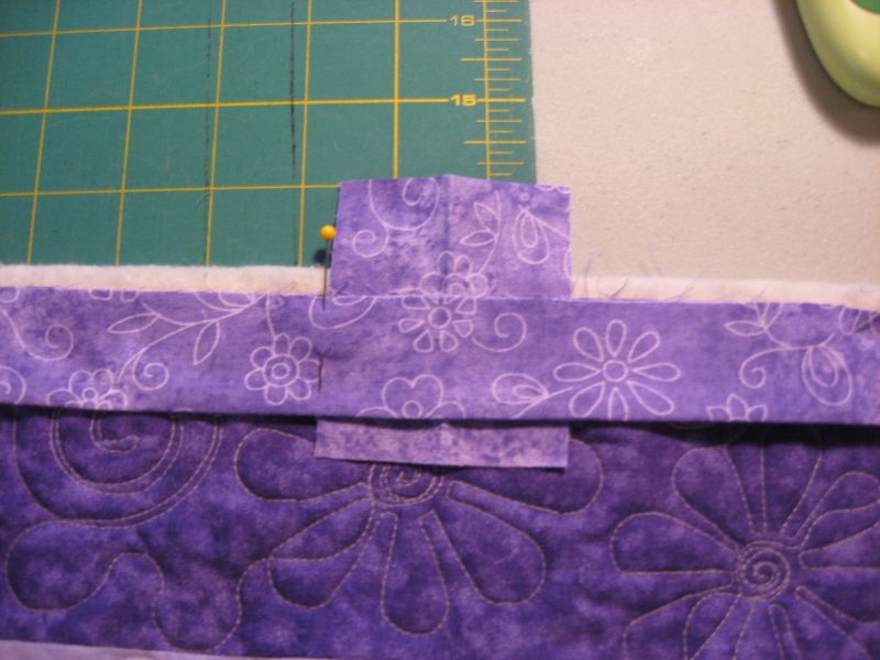 lay the tail over the scrap binding and place a pin in the binding