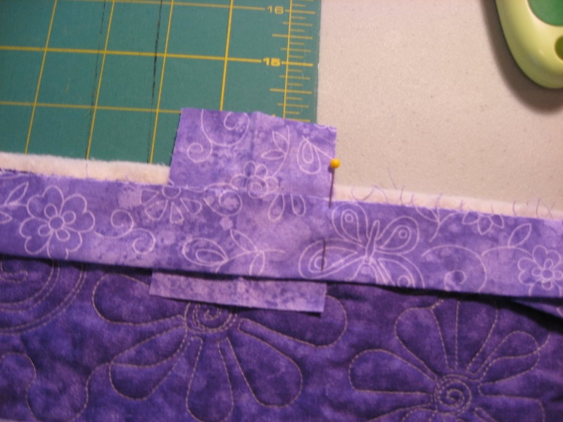 lay the end tail over the scrap binding and place a pin in the binding